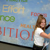 On Friday, October 18, during its fifth anniversary celebration, the NYA staff unveiled muralist Nichole Blackburn's donation of artwork covering the recreation and community facility's walls. Newtown Youth Academy Director of Communications Alisa Farley writes on the conference room walls that have been painted as a dry-erase board, part of the murals of encouraging words behind her in the NYA conference room and elsewhere in the facility. (Bobowick photo)