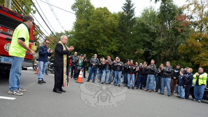 Monsignor Robert Weiss addresses the group of motorcycle riders, saying a prayer for them and for the first responders who will benefit from the Fourth Annual Firehouse Ride. (Bobowick photo)