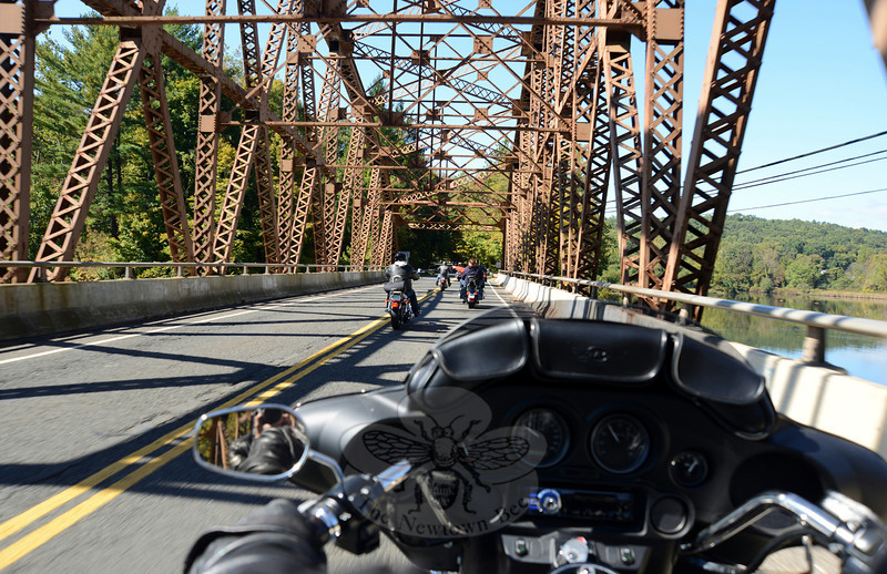 The group of roughly 100 motorcycles on the Fourth Annual Firehouse Ride passes from Southbury and into Newtown via the Silver Bridge leading to Glen Road. (Bobowick photo)