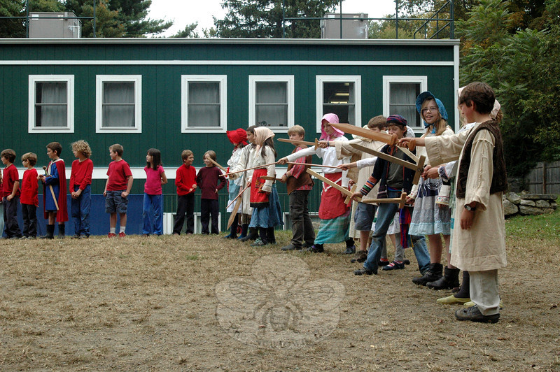 Housatonic Valley Waldorf School's fifth graders dressed as villagers for a play performed during the school's annual Michaelmas Festival. The students all draw swords up high, ready to defeat a dragon as it approached them. (Silber photo)