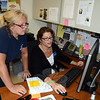 Town Clerk Debbie Aurelia-Halstead, seated, works with Animal Control Officer Carolee Mason demonstrating new software now available to police, dispatch, animal control, and shelter personnel. The town clerk said Newtown's vendor for recording land records, maps, trade names, indexing vitals, and dog licensing has created a internal search database for registered dogs. Now officials can search for or identify a dog by tag, last name, breed, or street address going back eight years. They can also identify stray dogs from other towns as long as those town clerks are set up with the same vendor. There are currently 52 towns in Connecticut using this system. (Voket photo)