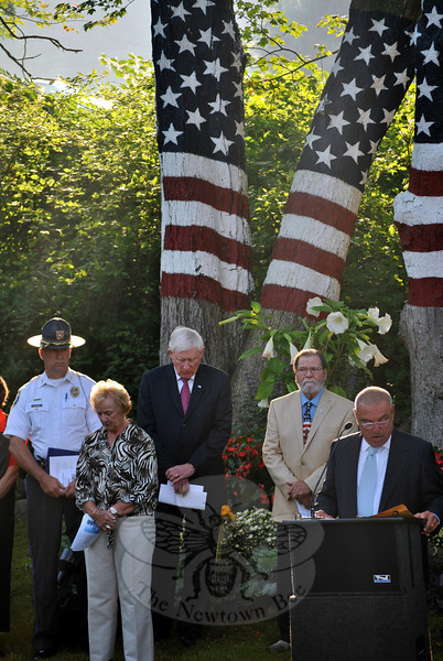 """Honoring those who died 9/11, Newtown Police Chief Michael Kehoe called the day an """"anniversary of tragedy and triumph,"""" in remarks made Wednesday morning, September 11, to nearly 100 people, including Newtown State Representative Mitch Bolinsky, gathered on the Route 302 property of former American Stock Exchange trader Howard Lasher. Pictured from left, Chief Kehoe, Newtown First Selectman Patricia Llodra, WestConn President Dr James Schmotter, and artist David Merrill listen as Mr Lasher offers words of hope and  consolation. In opening remarks, Mr Lasher noted, """"On December 14, 2012, we suffered our own 9/11,"""" and took time to pay homage to Mrs Llodra, the Newtown Police Department and fire companies, first responders, and all who """"helped our town come together."""" In later remarks, Mr Lasher pointed out, """"Twelve years after the 9/11 attacks, we strive to find hope,"""" adding that that there are no words, ceremonies, plaques, or tears that will ever return those lost that day. (Crevier photo)"""