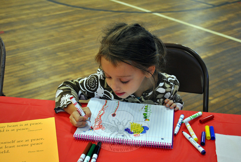 Four-year-old Rusa Ellul practices her peace flag designs on a piece of paper at Saturday morning's Kids Day of Service co-sponsored by Whole Foods Market and Sandy Hook Peaceful Arts. Rainbows, vines, and roses were all options for Rusa. (Crevier photo)