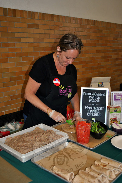 Sam Popalardo, the healthy eating specialist for Whole Foods Market in Fairfield, prepares bean and greens tortilla wraps for participants at the Kids Day of Service. (Crevier photo)