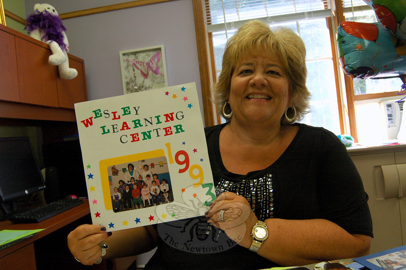 Wesley Learning Center Director Rahnna Peck holds a photo of the school's first class from 1993. Wesley Learning Center is celebrating its 20th anniversary this year. (Hallabeck photo)