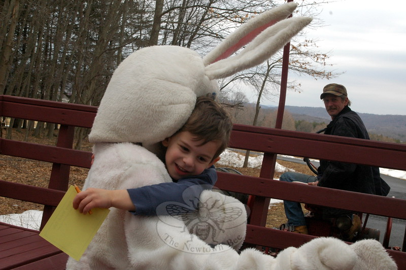 Owen Stoltz received a hug from the Easter Bunny on April 3, during a wagon ride while driver Milton Adams looked on. (Hallabeck photo)