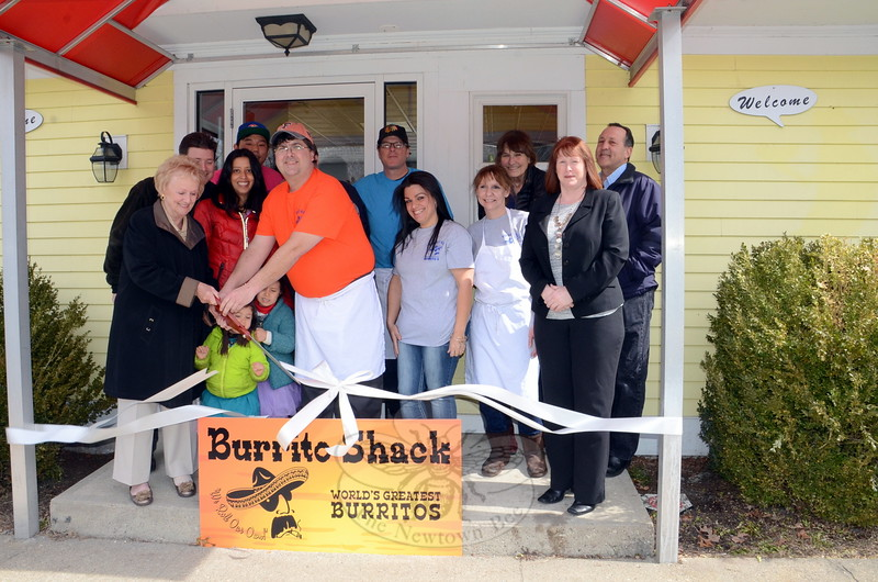 """Newtown First Selectman Pat Llodra, far left, helps Burrito Shack owner """"Johnny Baby"""" Wilson with the big scissors as he, his family, and staff celebrated the official ribbon cutting at their new restaurant at 314 South Main Street. The Burrito Shack officially opened March 9. (Voket photo)"""