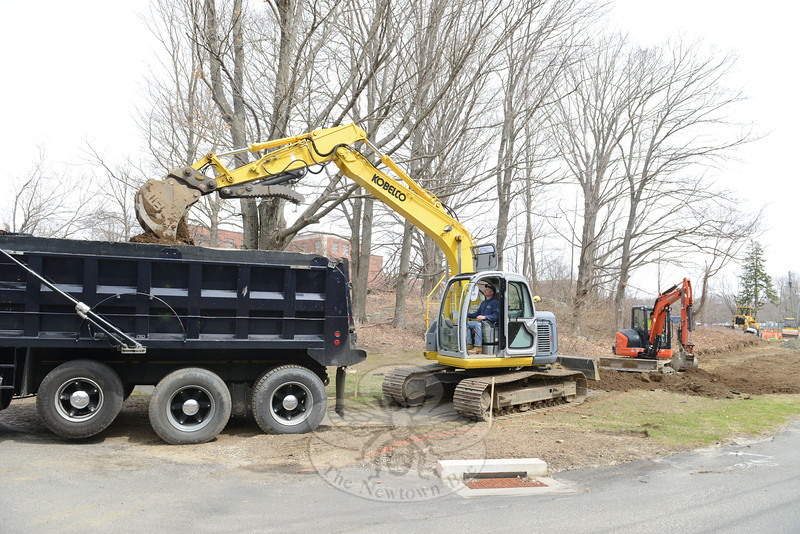 Rob Manna drops a bucketful of fresh-dug soil into a dump truck as he and Ryan Clark, working the backhoe on the right, prepare the foundation Tuesday for what will be a paved trail surface at Fairfield Hills. They began their project Monday. (Bobowick photo)