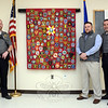 Brian Gregorio, second from right, presented to town police on April 15 a banner containing scores of police patches from law enforcement agencies across the state and country. Mr Gregorio donated the display in honor of the Newtown Police Department's efforts following the December 14, 2012, shooting incident at Sandy Hook Elementary School. Receiving the banner on behalf of local police are Administrative Sergeant Aaron Bahamonde, right, and Officer Jason Flynn. The Newtown Police Department's shoulder patch is surrounded by other patches on the banner.                                                     (Gorosko photo)