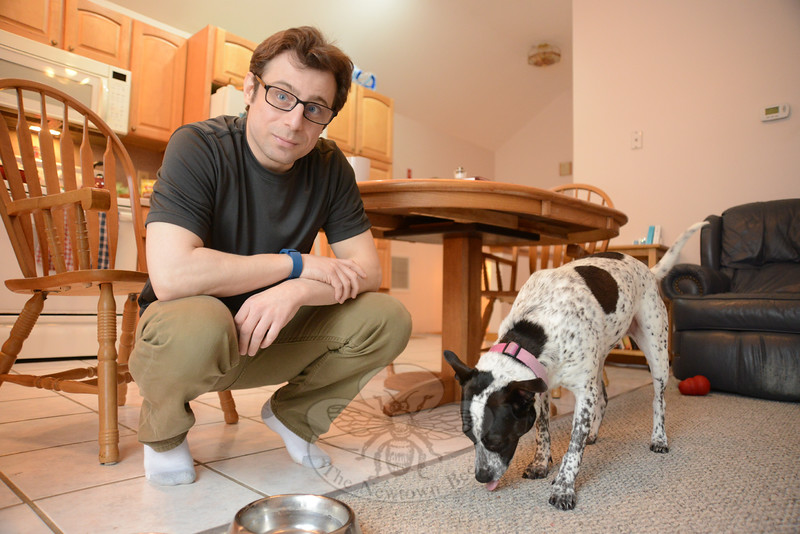 Michael Vastarelli leans down to play with Cookie, his rescue pet and companion who shares his Newtown apartment. Late this winter Mr Vastarelli spoke about his life after a kidney disease diagnosis in 2006, and life with dialysis since 2013. He is now waiting for a kidney donor through Yale New Haven Hospital. (Bobowick photo)