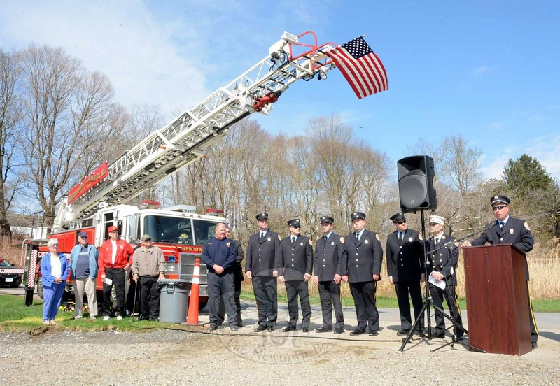 A US flag extended from Newtown Hook & Ladder's ladder truck blew in the breeze as Rob Manna of Hook & Ladder, right, spoke at groundbreaking ceremonies for a new firehouse at 12 Church Hill Road. (Gorosko photo)