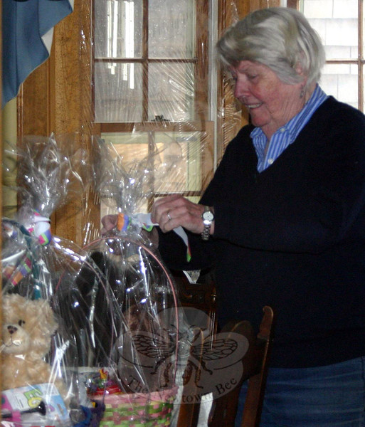 For years, Women Involved in Newtown have created Easter baskets and decorated candy bags to distribute to area children and young adults in need. This year the group was helped by The Rainbow Peace Girls, a group of Middle Gate Elementary School fourth graders who did their own collection of stuffed animals and plastic grass for the WIN project. The girls dropped off the final collection of items donated by their classmates on March 26, the same day members of WIN spent a few hours at the Monaco home assembling baskets. This year WIN provided 56 baskets and 15 candy bags to Newtown Social Services, 30 baskets to AIDS Interfaith Ministry in Danbury, 12 baskets and 35 candy bags to Healing Hearts Center For Grieving & Loss in Danbury, and 20 baskets to St Rose of Lima Church in Newtown. Shown, WIN member Dot Dwyer tidies a ribbon on one of this year's baskets before it was sent out for delivery. (Hicks photo)