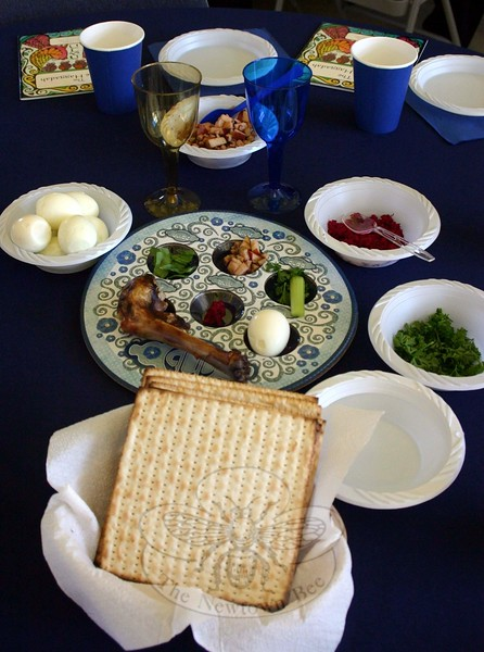 """Guided by Rabbi Shaul Praver, members of the Newtown Interfaith Clergy Association were joined by a few dozen members of the public for the 2015 Interfaith Seder on March 29. This year's event, which has been rotating among the town's houses of worship in recent years, was hosted by Newtown Congregational Church. Rabbi Praver sat near the center of the head table, joined by fellow local clergy members in the public event. Seated at the head table this year, as seen above during a ceremonial washing of their hands, from left, were Monsignor Robert Weiss, Reverend Leo McIlrath, Reverend Mel Kawakami, Rabbi Praver, Pastor Kathie Adams-Shepherd, John Woodall, Reverend Caroline Hamil-ton-Arnold and Reverend Matthew Crebbin. In the upper photo at far right is Rabbi Praver signing Birkat Hamazon (blessing of the nourishment), with Rev Kawakami, from Newtown United Methodist Church, on the left. At right, Elijah's cup was filled at each table. The Seder took nearly two hours, and that was for a gathering that did not include the full Passover meal, which Rabbi Praver described as """"usually being quite a spread"""" with the traditional gefilte fish and lamb, among other dishes. Sunday's Seder did include all of the sacred ritual items, however, with each table receiving a Seder plate (shown) with the six traditional items of bitter herbs (celery leaves and horseradish, in this case), charoset, parsley, a hard boiled egg, a roasted lamb shankbone, and, placed in front of the ceremonial plate, whole matzot. At the end of the meal, the 51 attendees joined the local clergy to close with """"Next year in Jerusalem,"""" before Rabbi Praver encouraged """"Let's all go from this Seder and try to do better."""" Visit NewtownBee.com for an expanded story and additional photos from last weekend's event. (Hicks photo)"""
