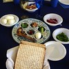 "Guided by Rabbi Shaul Praver, members of the Newtown Interfaith Clergy Association were joined by a few dozen members of the public for the 2015 Interfaith Seder on March 29. This year's event, which has been rotating among the town's houses of worship in recent years, was hosted by Newtown Congregational Church. Rabbi Praver sat near the center of the head table, joined by fellow local clergy members in the public event. Seated at the head table this year, as seen above during a ceremonial washing of their hands, from left, were Monsignor Robert Weiss, Reverend Leo McIlrath, Reverend Mel Kawakami, Rabbi Praver, Pastor Kathie Adams-Shepherd, John Woodall, Reverend Caroline Hamil-ton-Arnold and Reverend Matthew Crebbin. In the upper photo at far right is Rabbi Praver signing Birkat Hamazon (blessing of the nourishment), with Rev Kawakami, from Newtown United Methodist Church, on the left. At right, Elijah's cup was filled at each table. The Seder took nearly two hours, and that was for a gathering that did not include the full Passover meal, which Rabbi Praver described as ""usually being quite a spread"" with the traditional gefilte fish and lamb, among other dishes. Sunday's Seder did include all of the sacred ritual items, however, with each table receiving a Seder plate (shown) with the six traditional items of bitter herbs (celery leaves and horseradish, in this case), charoset, parsley, a hard boiled egg, a roasted lamb shankbone, and, placed in front of the ceremonial plate, whole matzot. At the end of the meal, the 51 attendees joined the local clergy to close with ""Next year in Jerusalem,"" before Rabbi Praver encouraged ""Let's all go from this Seder and try to do better."" Visit NewtownBee.com for an expanded story and additional photos from last weekend's event. (Hicks photo)"