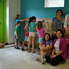 Lauren and Andrew Smiley, Ben and Emi Rosenthal, and Fiona Sullivan experiment with the Mag Wall at EverWonder Children's Museum Experience, made possible by a donation from the Newtown Junior Women's Club. Standing, from left, are NJWC member Meri Jitsukawa Rosenthal and EverWonder founder Kristin Chiriatti. Kneeling, NJWC member Sue Belanger and EverWonder Board of Directors member Karen Smiley.  (Crevier photo)