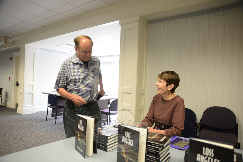 Pat Barkman, another Newtown author, shares a laugh with George Rockwell as she staffs the book table at the August 8 Mathieu Callier book reading.(Bobowick photo)