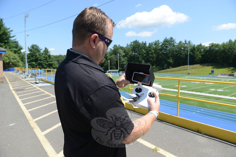 With a glance at his controls, which includes the use of his smartphone, Aaron Johnson guides his drone on a flight path above the football field. He operates the drone with two joysticks on the remote control to change elevation and direction, while a his phone provides a live camera view. (Bobowick photo)