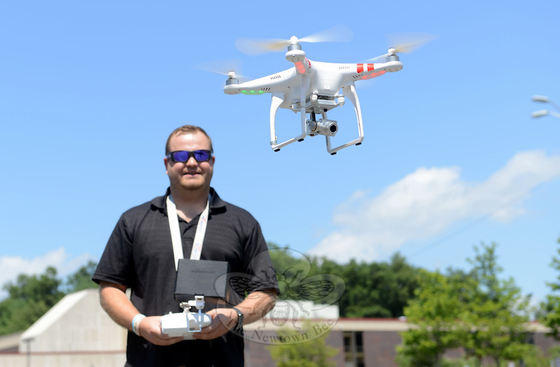 The DJI drone begins its flight path out of the parking lot toward the football field at Newtown High School Tuesday as Aaron Johnson guides it.	(Bobowick photo)