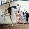 Summer Youth Employment Program students, from left, Rosie Rosado, Ann Butler, Samantha Crespo, and Misha Prudhomme, worked on Tuesday, July 28, to paint a wall at Newtown High School, just one of the many projects students in the program are overseeing this summer. (Hallabeck photo)