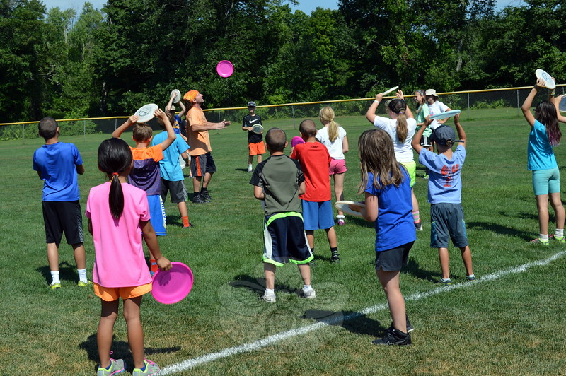 Todd Brodeur, back left center, demonstrated and taught Newtown Parks & Recreation day campers at Dickinson Memorial Park on Monday, August 3, a few tricks with Frisbees after presenting stories and some Frisbees from his personal collection. Mr Brodeur of World Class Frisbee Shows, a two-time world freestyle champion, according to his website, also visited with day campers at Treadwell Park on Monday after his visit to Dickinson. More information about Mr Brodeur is available on his website, frisbeeshows.com. (Hallabeck photo)