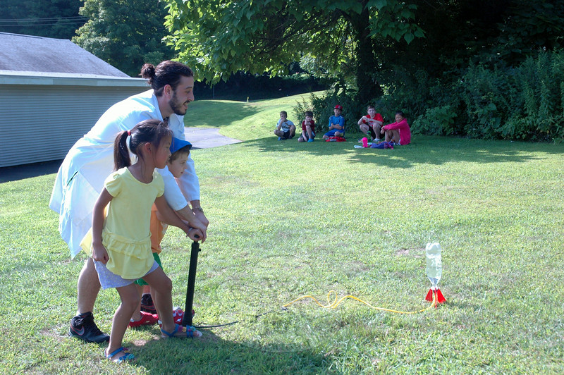 High Touch High Tech, Science Made Fun's Christopher Cellini, left, helped students pump air into a water bottle rocket on Thursday, August 7.  (Hallabeck photo)