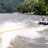 Tom Murphy and his son Eamonn of Brookfield enjoy a tube ride Thursday, July 31. Behind them is a dock where other water sport clinic participants wait their turns on the lake. (Bobowick photo)
