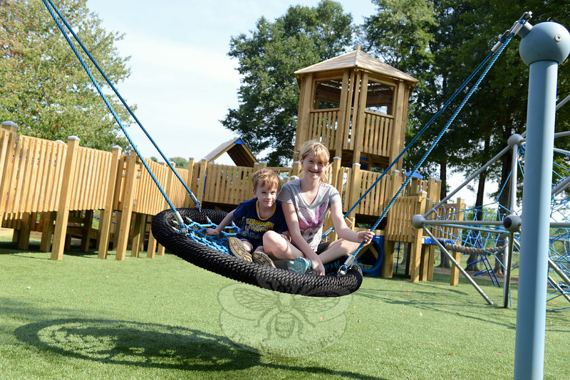Tyler and Morgan Drap swing and cast a weblike shadow from their perch on a new playground feature. Behind them is the playground's main network of walkways, slides, stairs, rope features, and more. (Bobowick photo)