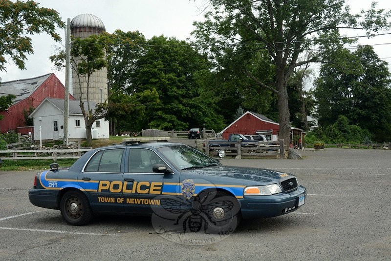 A town police officer within a patrol car was stationed on the morning of Tuesday, August 12, at Ferris Acres Creamery at 144 Sugar Street (Route 302). The rustic dairy bar's parking lot became the staging area for police during their lengthy search early this week for a missing elderly man, who was later found unharmed. (Gorosko photo)