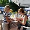 Quinn Murphy applies a decorative henna tattoo to Grace Zulli's hand at a Sound Center wellness fair event. (Bobowick photo)