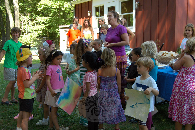 "Housatonic Valley Waldorf School Camp Director Carrie Reilly, standing center, led a group of the school's summer campers through singing a ""snack blessing"" before a harvest feast celebrating the school's summer camps began on August 14. (Hallabeck photo)"