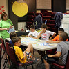 "Grace Family Church welcomed 151 children to its Vacation Bible School last week. This year's theme celebrated ""how God created everything, and how what God teaches us can be partnered with what science tells us,"" explained GFC Children & Youth Pastor Adam Fredericks. Presented August 10-14, the annual event offered lessons and games, and crafts for ages 4-12. VBS culminated on Friday with a picnic lunch, where families were invited to join together with VBS leaders for a final celebration of the lessons learned during the week. Donna Guerrera, standing, listens while a young man makes a point during a lesson/discussion. (Hicks photo)"