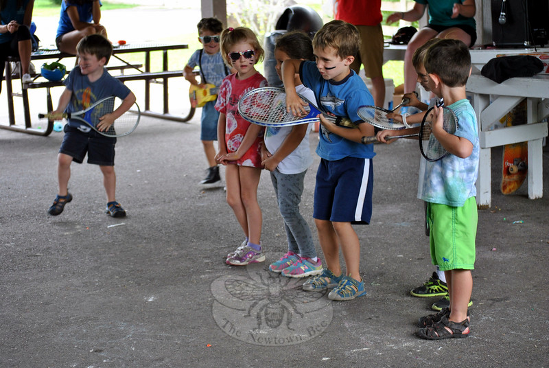 "Tiny Tot campers from Dickinson Day Camp rock out with racket ""guitars,"" entertaining family and friends at the end-of-year talent show. (Crevier photo)"