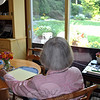 "Author Sydney Eddison contemplates her garden, seated at her kitchen table. ""… In the ticking of the kitchen clock, the hum of the refrigerator, and the soft exhalation of a sleeping dog, I hear the message That all is well today. The words will come."" ~From ""The Message"" by Sydney Eddison. (Crevier photo)"