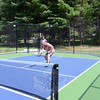 Gavin Preis follows through on his swing to send the ball back at his opponents Wednesday at Treadwell Park, while his partner Terrell Harris, background, is ready to return a hit to his side of the court. The men are playing pickleball, which now has a new court in Newtown since upgrades to Treadwell last year. (Bobowick photo)