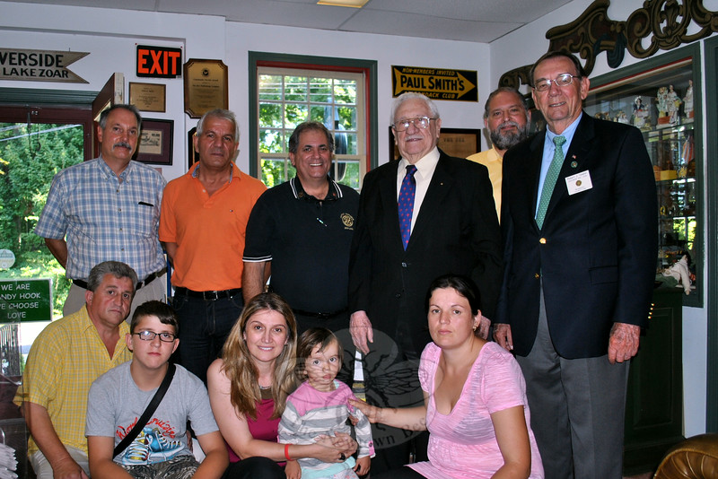 Area Rotary members pose in the office of The Newtown Bee, along with two children sponsored for heart surgery by the Newtown Rotary Gift of Life Initiative. From left, front, Jusuf Lajqi and son, Ar-ben Lajqi, Albana Krasmiqi holding Leona Hoti, and Leona's mother, Hikmete Ymeraj. Back row, Newtown Rotary member Pat Caruso, Nasar Behluli, George Solomon, former vice president of Rotary International Abraham Gordon, Joe DeVincent, and former Rotary district governor Robert Vossler. (Crevier photo)