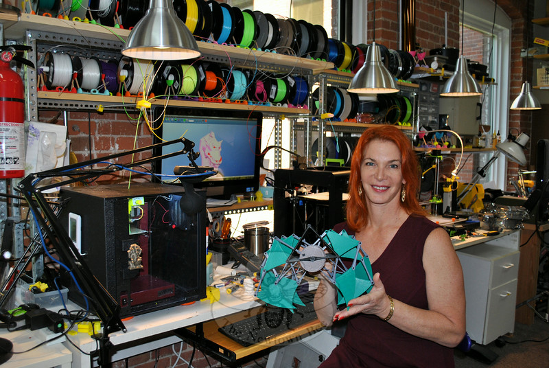 "Julia Truchsess, founder and president of Pragmatic Designs, Inc, holds a miniature version of artist Theo Jansen's ""Strand Beest,"" which she made on a 3D printer. Ms Truchsess sees the value of the new 3D printing in her business, as well as for hobbyists enthused to experiment with new technology. (Crevier photo)"