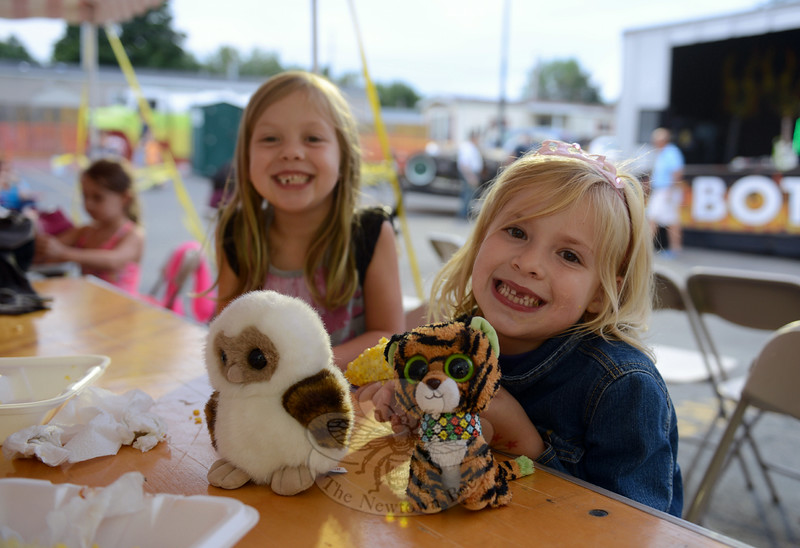 Carly Galligan, left, and Tierney Lee grab a quick summer treat of corn on the cob that they share with their stuffed animal friends during the Botsford Bash. (Bobowick photo)