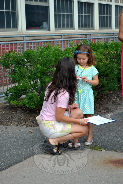 Hawley School kindergarten teacher Annie Fries greets one of her students, Clare Csaszar, Friday morning, August 22. Clare and her classmates-to-be had the opportunity to ride the bus to school in preparation for the first day of school, August 26. (Crevier photo)