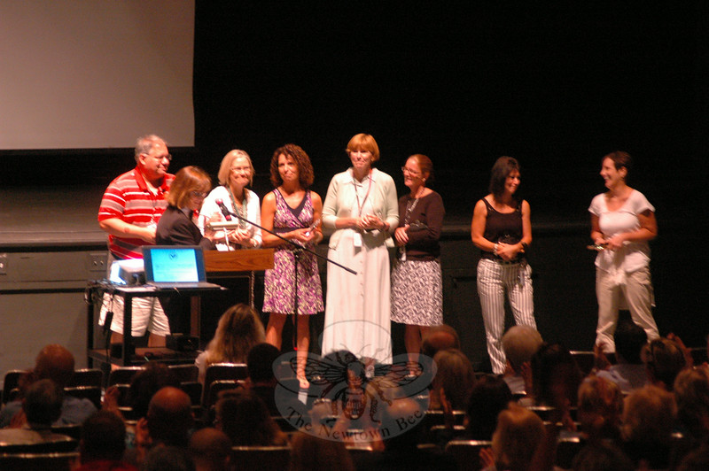 Teachers who are beginning their 25th school year with Newtown were honored during the August 21 convocation ceremony at Newtown High School. Assistant Superintendent of Schools Linda Gejda, second from left, announced each honoree before all were greeted by Board of Education members and stood before the crowd at the ceremony. (Hallabeck photo)