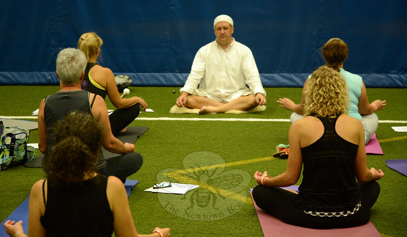 Yoga instructor Chris Smith, center, presides during a session of Kundalini yoga at the Newtown Yoga Festival. The meditative Kundalini yoga seeks to energize and revitalize the body. (Gorosko photo)