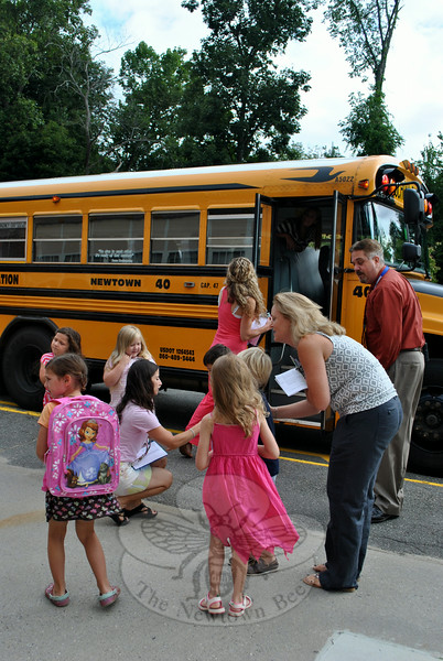 Kindergarten teachers Annie Fries, kneeling, Donna Albano, right, Deborah Pond, at the bus door, and new Hawley School Principal Chris Moretti, greet kindergartners as they disembark Bus 40, Friday morning, August 22. (Crevier photo)