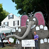 "Dr Joshua Baum stands next to the oversized reminder ""Brushing Your Teeth Is Never Irr-Elephant,"" built from nine large hay bales, on the front lawn of the 23 Church Hill Road orthodontics office. (Crevier  photo)"