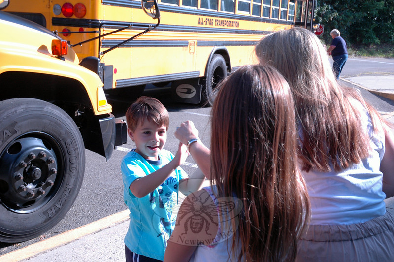 Sandy Hook School kindergartener Antonio Arguello, left, received a high-five from his mother, Jennifer, after his first ride to school on a bus. His sister Gabbi was also there to greet him. (Hallabeck photo)
