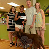 Coco, foreground, an 11-year-old female chocolate Labrador retriever who is owned by Mandy Beckett, now wears the dogbone-shaped #1 Newtown dog tag for the 2014 dog-licensing year, having won that honor through a recent raffle conducted by Town Clerk Debbie Aurelia Halstead. Coco is authorized to wear that dog tag through next May. The raffle promotes local dog licensing. In honor of that #1 Dog status, Your Healthy Pet, a pet food, supplies, and accessories store at 224 South Main Street, awarded Ms Beckett a $50 gift certificate for store merchandise. Shown at the store are, from left, Ms Halstead, Ms Beckett, and store proprietors Tom Novak and Mary-Kay Novak. (Gorosko photo)