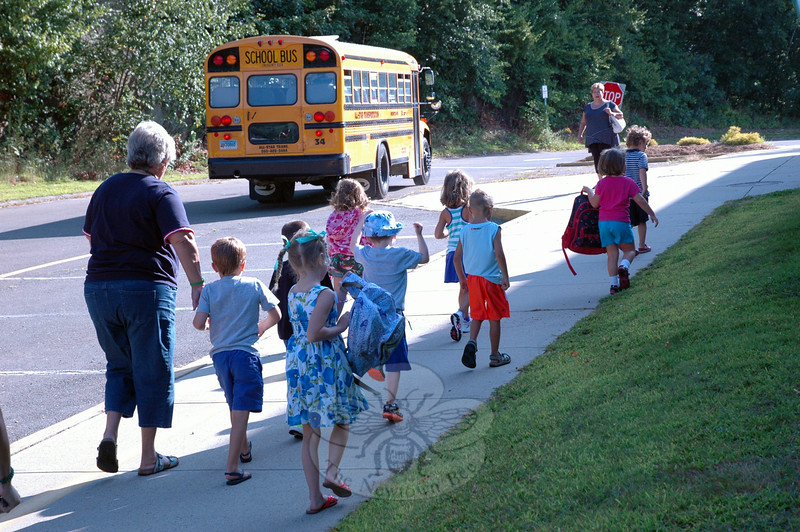 Sandy Hook School Secretary Joanne Didonato, far left, walked a group of kindergarteners toward their school on Friday, after their first ride on a school bus. (Hallabeck photo)