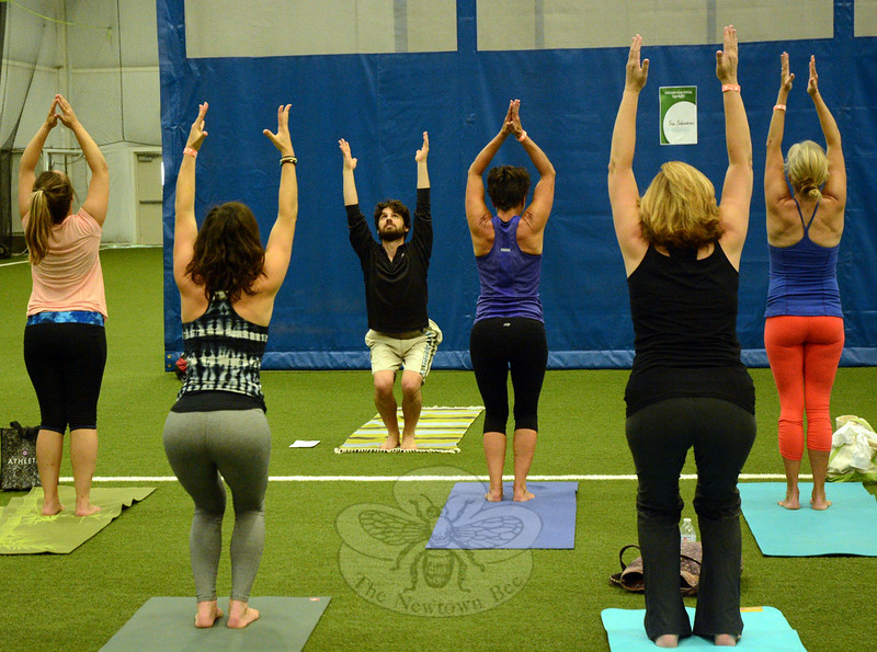 Under the guidance of yoga instructor Brian Pontolilo, third from left, a group of yoga participants demonstrates the chair pose. The instructional session was one of many held at the Newtown Yoga Fes-tival. (Gorosko photo)