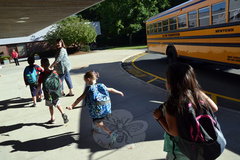 "Head O' Meadow librarian Bev Bjorklund led a group of students from their bus to the school on Thursday, August 27, for the first day of the 2015-16 school year. Inside the school teachers and staff waited to greet the students, and near the entrance physical education teachers Steve Dreger and Alex Amaru shared high-fives with students. Mr Amaru, who is new to the school, welcomed the students with a special, ""It's my first day, too!"" ""Welcome back everybody!"" Principal Barbara Gasparine said, smiling as students stepped off a bus. Across the district students arrived for the first day on Thursday. (Hallabeck photo)"