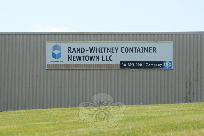 As seen from Edmond Road, a large banner hangs on the steel eastern wall of Rand-Whitney Container Newtown, LLC, a large factory where corrugated cardboard containers are made.  The firm received two zoning variances from the Zoning Board of Appeals on August 5 toward its goal of expanding the factory.(Bee Photo, Gorosko)