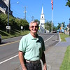 David Lydem stands on the sidewalk on Church Hill Road on July 31, the town's Main Street flagpole behind him. Mr Lydem has stepped down as the facilitator of the flagpole after 31 years of spearheading the maintenance and upkeep of the landmark pole and the flags that fly from it.  (Bee Photo, Hicks)