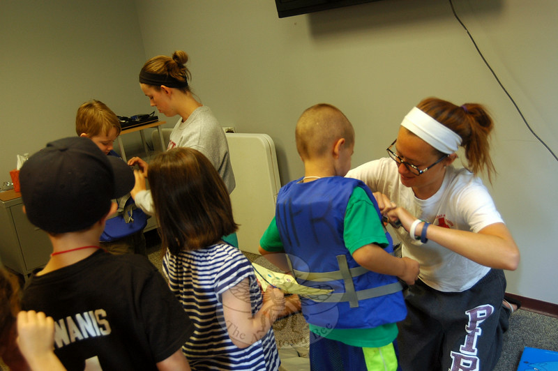 Newtown Parks & Recreation life guards Megan Duero, back left, and Jenn McDonald, right, showed Newtown Youth & Family Services (NYFS) Safety Town students how to wear life vests on Thursday, July 31. (Hallabeck photo)